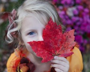 Young girl holding autumn leaf against her face